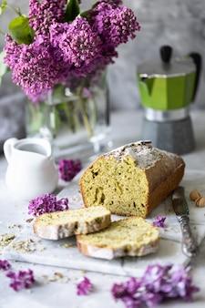 Торт с фисташками и шпинатом с чашечкой кофе с букетом сирени на столе. копировать пространство