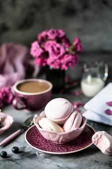 暗いテーブルの上の黒いボウルにマカロンケーキの形でマシュマロとガラスの花と朝食のコーヒーカップ