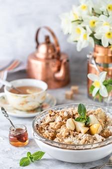 焼き洋ナシと洋ナシとハチミツが入ったテーブルの白い皿に銅の道具と花が入っています