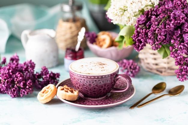 朝食一杯のコーヒー、ワッフル、牛乳、クリーム、ライラックの花。朝