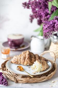 Завтрак французский круассан, джем, чашка кофе, молоко с кремом и сиреневые цветы. утро