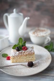 木製のテーブルにカプチーノカップとベリーとミントのプレートでナポレオンデザート。