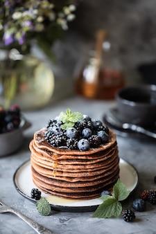 テーブルの上に粉砂糖と野生の花の花束が飛んで、ベリーと蜂蜜とフルーツのチョコレートパンケーキ。闇