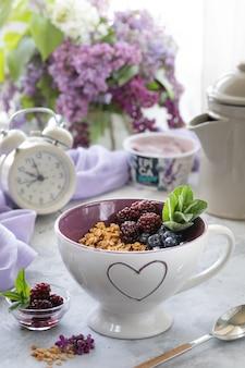 ライラックの花束と窓の近くのテーブルの上の果実とホームグラノーラ。