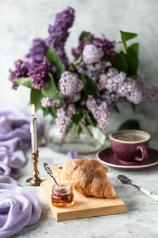 Круассаны натюрморта и чашка кофе и букет сирени на столе у окна.