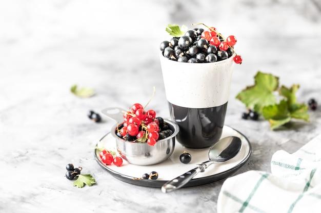 セラミックカップの新鮮なスグリ:黒スグリ、赤スグリ、セレクティブフォーカス。テキストのための場所。コピースペース