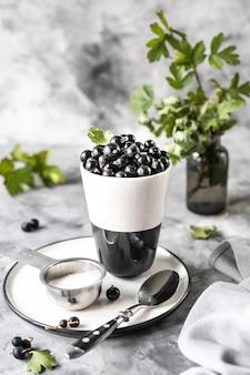 セラミックカップの新鮮なスグリ:黒スグリ、セレクティブフォーカス。テキストのための場所。コピースペース