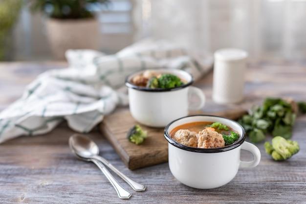 木製のテーブルの上の金属のマグカップでミートボールのスープ