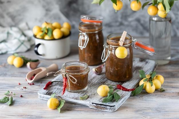 ガラスの瓶に新鮮な黄色いプラムのソース。新鮮な黄色い梅梅。ガラス瓶入りの自家製ソース。トケマリ。