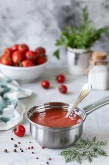 黒い皿の上のガラスの瓶に新鮮な赤いトマトのソース。白いテーブルに新鮮なチェリートマト、ニンニク、唐辛子、ディル、パセリの小枝。自家製ケチャップの缶。クローズアップ