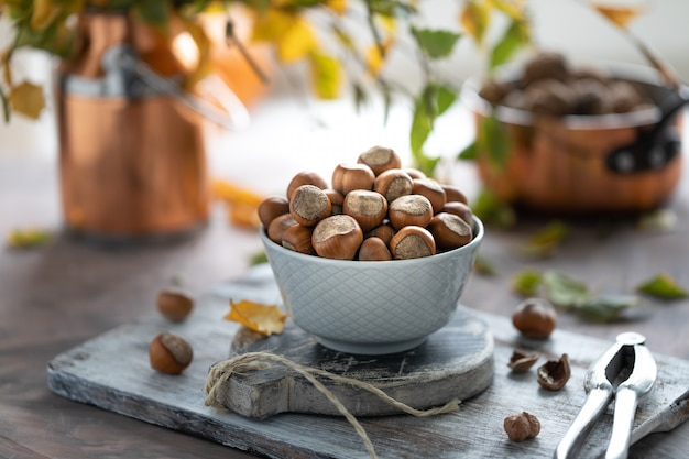 Лещинные орехи в керамической чашке на столе. осенний натюрморт