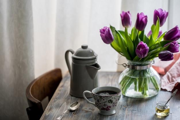 窓辺の花と木製のテーブルの上に蜂蜜とワッフル。