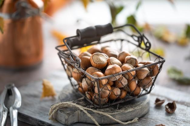 Орехи в плетеной металлической корзине на столе. осенний натюрморт