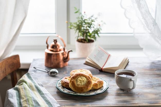 チーズケーキウィンドウで猫と木製のテーブルで朝食のロール