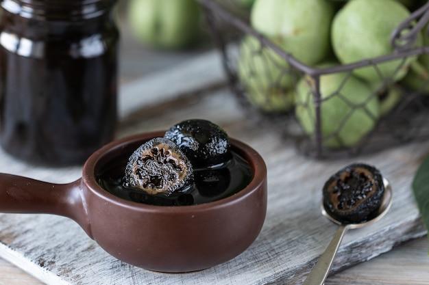 Баночка варенья грецкого ореха на деревянный стол и группа зеленых грецких орехов.