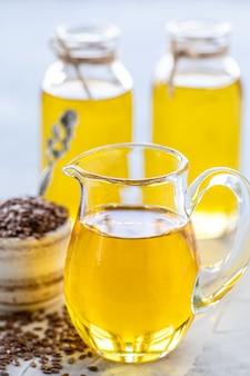 亜麻仁油のボトルと茶色の亜麻の種子と木のスプーンのセラミックボウル。垂直
