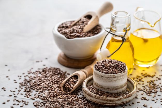 亜麻仁油のボトルとセラミックボウルに茶色の亜麻の種子と木のスプーン
