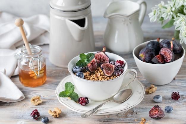 イチジク、ベリー、蜂蜜入りカッテージチーズ。一杯のコーヒーとコーヒーポット。朝ごはん。木製テーブル。