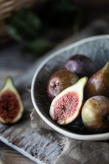 暗い木製のテーブルの上にボウルに新鮮な熟したイチジク。