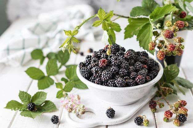 セラミックカップに新鮮な熟したブラックベリー。