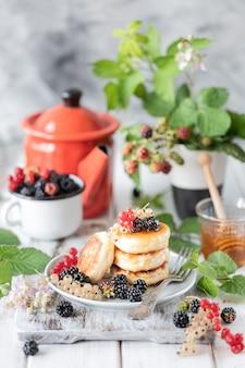 ベリーと白い木製の目覚まし時計の自家製パンケーキ