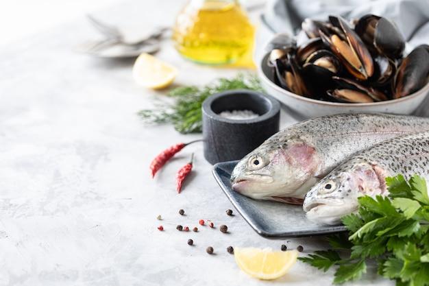 健康でおいしい食べ物を準備するための皿、野菜、新鮮な野菜の生のニジマス魚。