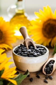 Подсолнечное масло в бутылочном стакане с семенами и цветами подсолнечника