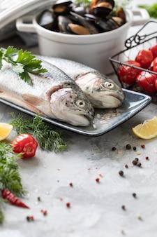 Сырая рыба радужная форель на тарелку, зелень и свежие овощи для приготовления здоровой и вкусной пищи. белая сковорода с мидиями на бетоне