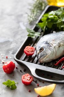 Сырая рыба дорадо со специями, лимоном и петрушкой в черной сковороде гриль на белом бетоне. здоровое питание и вкусная кулинарная концепция.