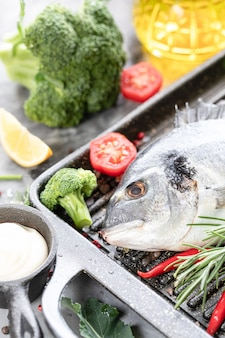 Сырая рыба дорадо со специями, лимоном и петрушкой в черной сковороде гриль на белом бетоне