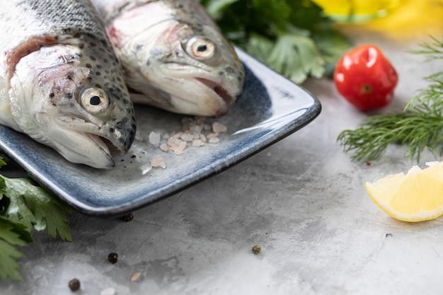 スパイス、レモン、パセリ、白いコンクリートの黒いグリル鍋で生ドラド魚