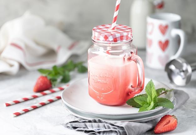 美しい赤いガラス瓶と白いコンクリートのテーブルにミントの小枝でイチゴとミルクまたはヨーグルトのスムージー。