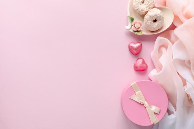 ノートパソコンと女性のアクセサリー、淡いピンクのテーブルの上の化粧品のファッションブロガーワークスペース。