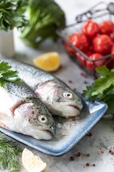健康でおいしい食べ物を準備するための皿、野菜、新鮮な野菜の生のニジマス魚。健康的な食事とおいしい料理のコンセプト。