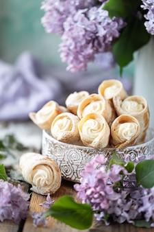 木製のテーブルにライラックの花束と春の静物画の金属箱にバニラクリームとパイ生地の角