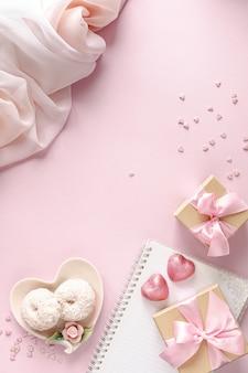 Подарочная коробка или подарочная коробка и цветы на розовом столе вид сверху.