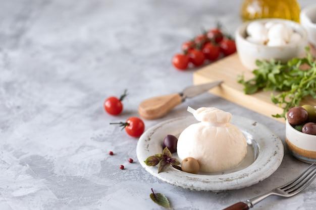 Итальянский сыр буррата на белой круглой тарелке и ингредиенты для салата
