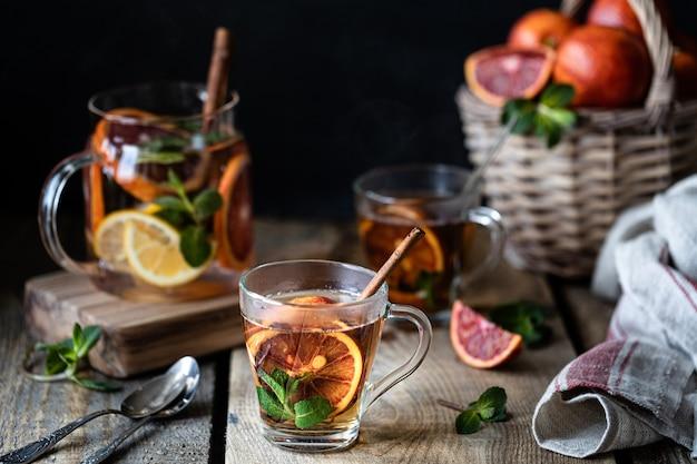 Домашний чай в прозрачном стакане с красным апельсином и лимоном, корицей и мятой на деревянном фоне. апельсины плетеная корзина
