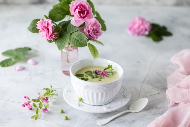 バラの花束と白い大理石の背景にグリーンピースのクリームスープ