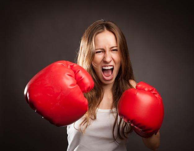 赤いボクシング用グローブを着た若い女性