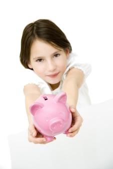 白で隔離される貯金箱を持つ若い女の子