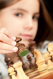Маленькая девочка играет в шахматы