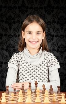 Маленькая девочка играет в шахматы на винтажной стене