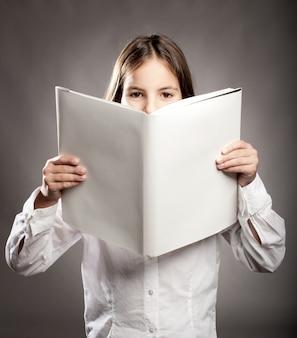 空白のカバーで本を読む小さな女の子