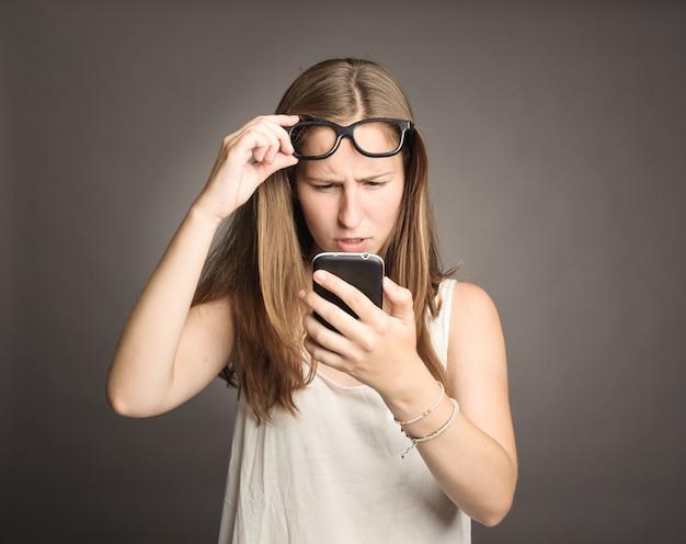 灰色の携帯電話を保持している若い女性