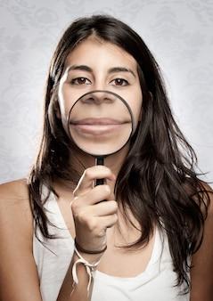 虫眼鏡を通して口を示す若い女性