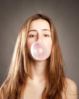 チューインガムから泡を作る若い女性