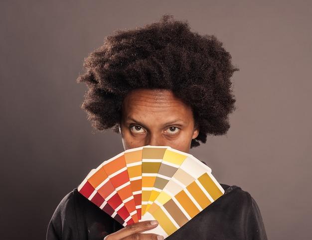 Женщина держит цветовую палитру на сером