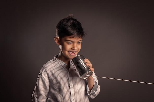 Малыш, используя банку как телефон на сером