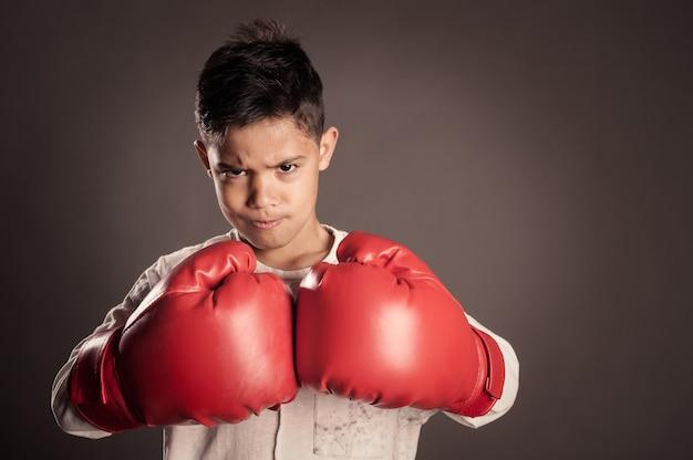 赤いボクシンググローブを着ている少年